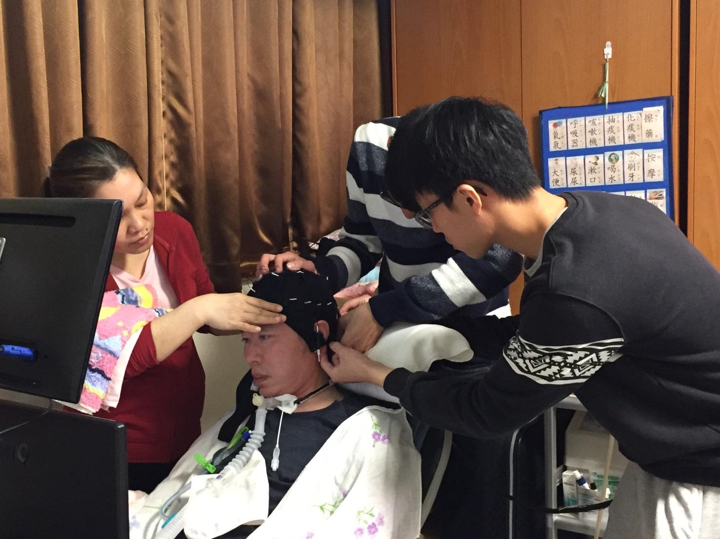 研發團隊為漸凍症患者劉老師戴上腦波帽,一旁看護在側確認劉老師的眼神,以確保是否有不舒服。(攝影/廖元鈴)