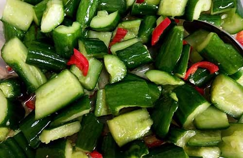 將鹽灑在小黃瓜上,拌勻後再加入辣椒、白醋及蒜粉拌勻。