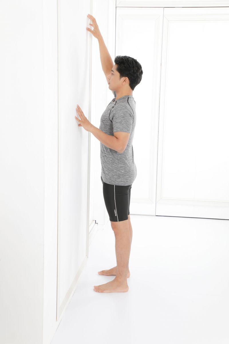 肘部略微彎曲,慢慢地將在牆面上的右手手指向上移動,像在牆面上走路一樣或像蜘蛛一樣一步一步向上爬。