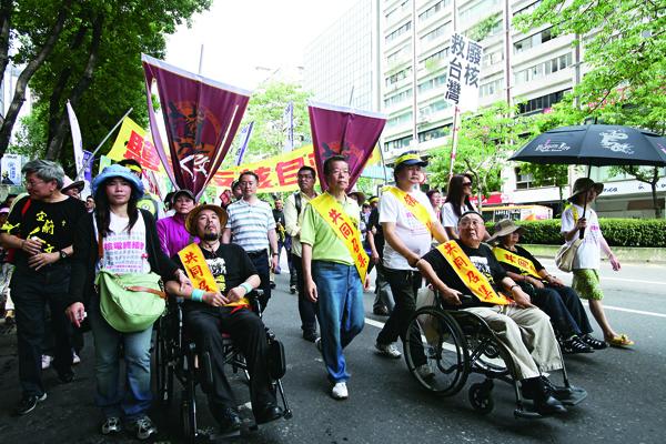 即使坐著輪椅,82歲的陳謨星(右一)為了阻擋核四毅然返台,站在 「終結核電大遊行」第一線。