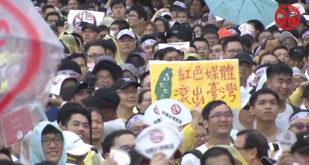 (民眾冒雨要親中媒體滾出台灣。圖/截自「飆捍」臉書直播影片)