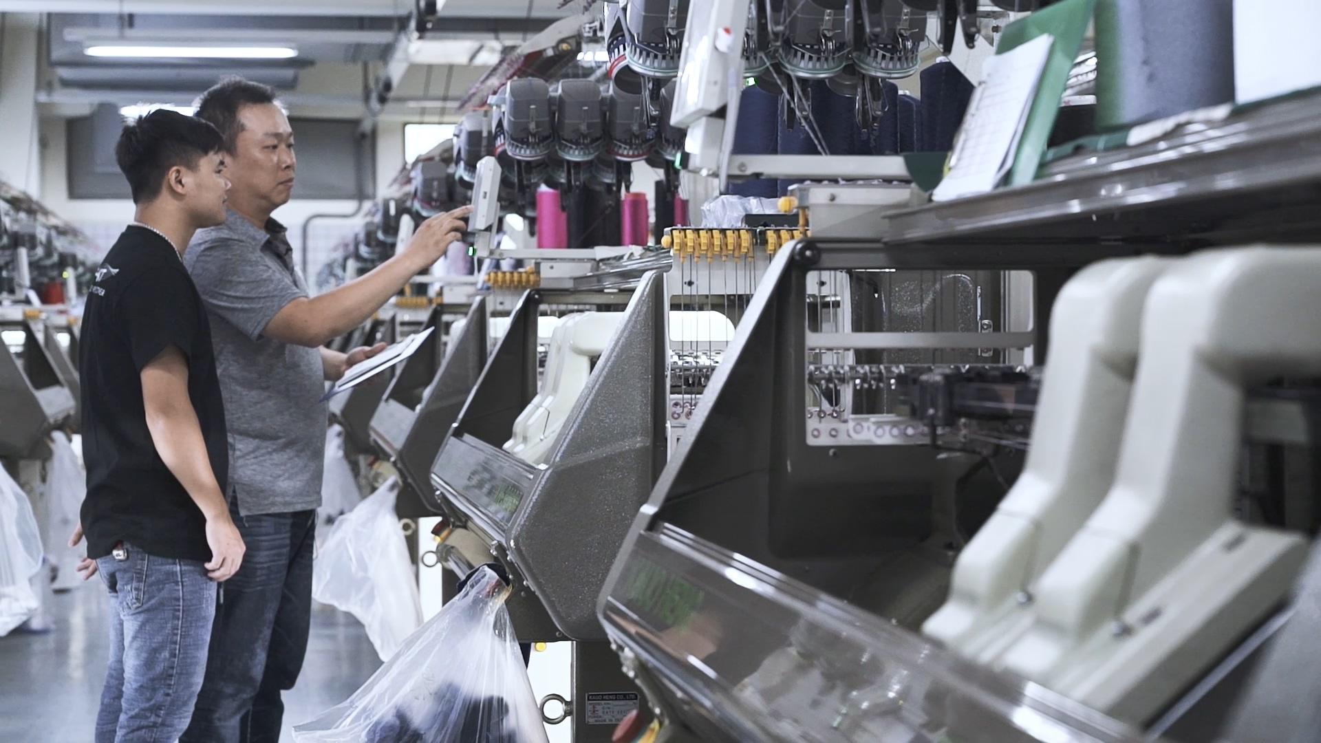 何尚傑正在操作製作編織鞋的編織機