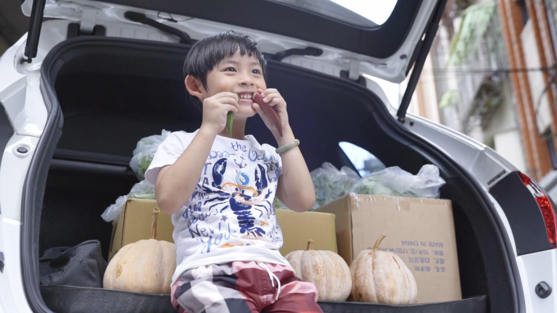 邱于恩在裝滿有機蔬菜的後車廂,調皮地拿著阿公種的秋葵做鬼臉