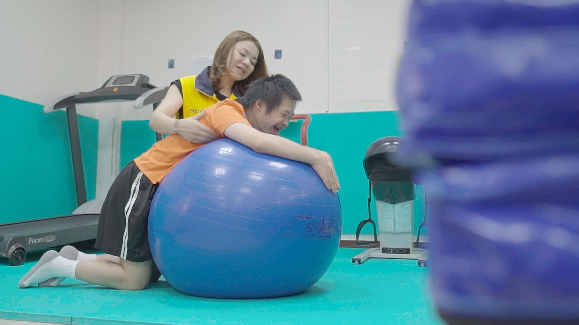 昇恆昌志工協助康福智能發展中心的孩子做跪姿訓練