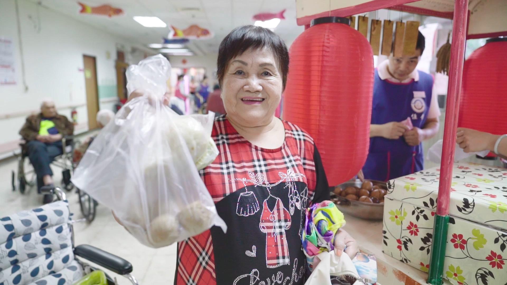 李賴員開心展示她在恆安市集中買到的茶葉蛋、水煎包。