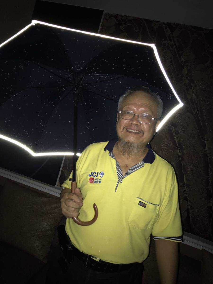 葉宗林手拿自己發明的反光傘,希望此產品能救到人