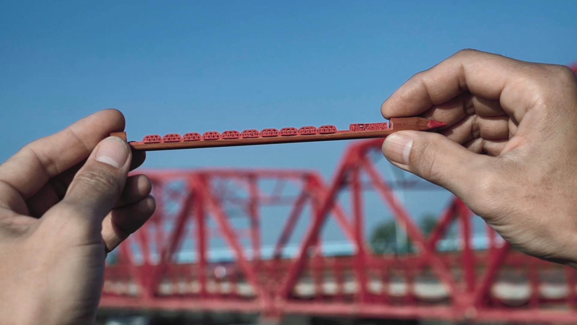 李健竹「西螺大橋」筆雕作品與雲林西螺大橋本尊合影。